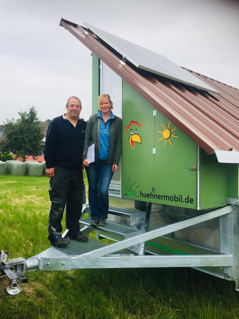 Holbergs vor einem Hühnermobil auf ihrem Bauernhof